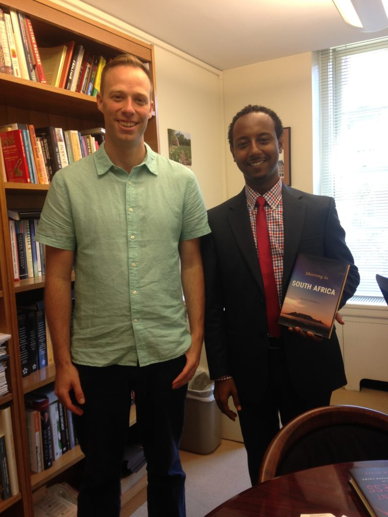 Nathan and Allen Grane, research associate, pose with Ambassador Campbell's new book, Morning in South Africa, which is used in IPED's South Africa course.